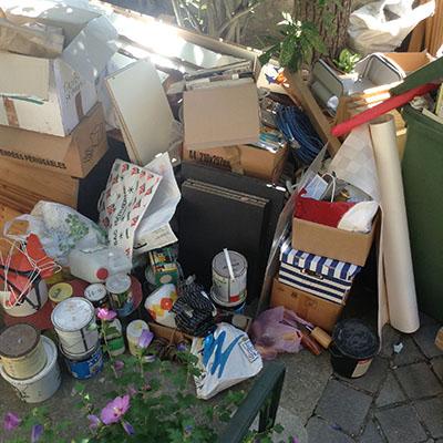 débarras maison Clamart pots de peinture, tiroirs, papier entreposés dans le jardin